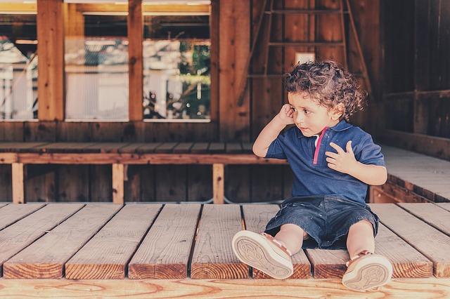 migraines in children, child sitting down touching head