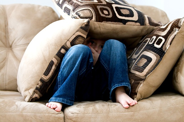boy with social anxiety disorder hiding under cushions on the couch